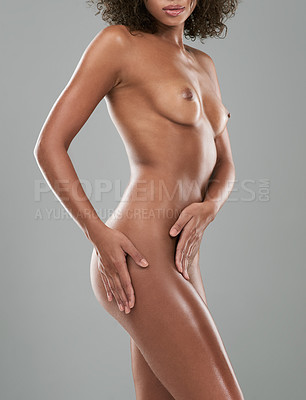 Buy stock photo Studio shot of an unrecognizable woman posing nude against a gray background