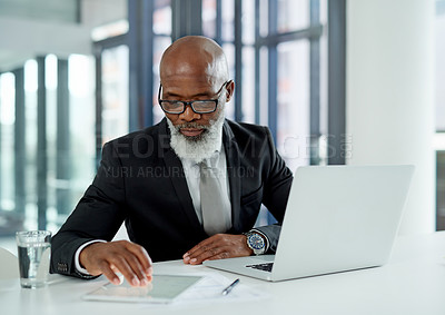 Buy stock photo Shot of a mature businessman working on a laptop and digital tablet in an office