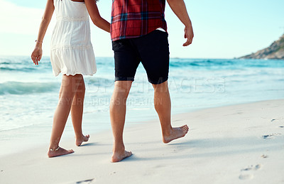 Buy stock photo Cropped shot of a young couple going for a romantic walk along the beach