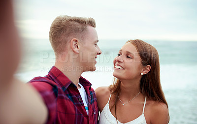Buy stock photo Shot of a happy young couple taking selfies at the beach