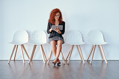 Buy stock photo Shot of a young businesswoman using a digital tablet while in line waiting against a white background