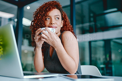 Buy stock photo Shot of a young businesswoman enjoying a cup of coffee while working in an office