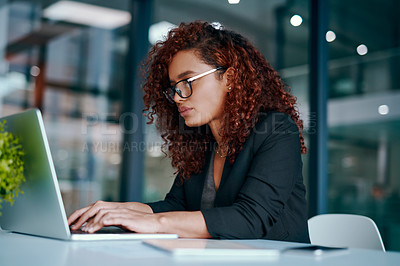 Buy stock photo Shot of a young businesswoman using a laptop in an office