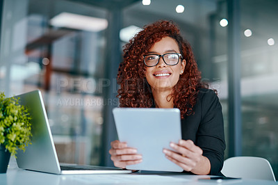 Buy stock photo Shot of a young businesswoman using a digital tablet and laptop in an office