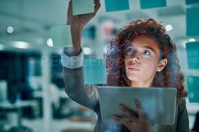 Buy stock photo Shot of a young businesswoman using a digital tablet while writing notes on a glass wall in an office