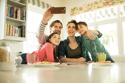 Buy stock photo Shot of a happy family taking selfies together at home
