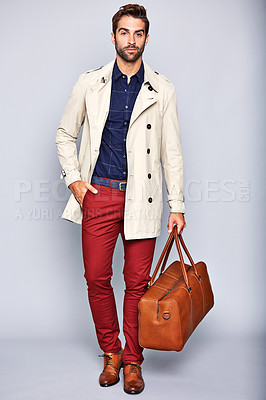 Buy stock photo Studio portrait of a handsome young man carrying a suitcase against a grey background
