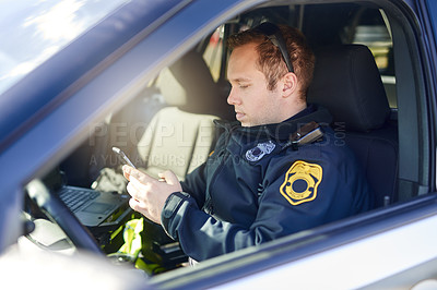 Buy stock photo Cropped shot of a handsome young male police officer using his cellphone while out on patrol