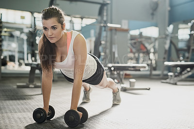 Buy stock photo Shot of a young woman working out with weights at the gym