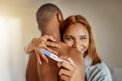 Buy stock photo Cropped shot of a young couple looking happy after taking a home pregnancy test