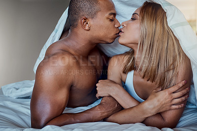 Buy stock photo Shot of an affectionate young couple sharing an intimate moment in bed