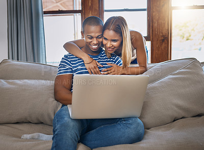 Buy stock photo Shot of a happy young man using a laptop on the sofa while his wife hugs him from behind