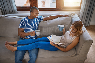 Buy stock photo Shot of a young woman reading a book while relaxing with her husband on the sofa at home