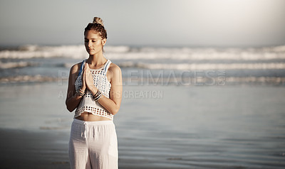 Buy stock photo Cropped shot of an attractive young woman practicing yoga on the beach