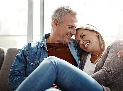 Buy stock photo Shot of an affectionate mature couple relaxing together on the sofa at home