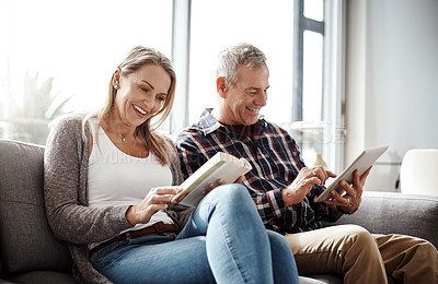 Buy stock photo Shot of a mature woman reading a book while her husband uses a digital tablet on the sofa at home
