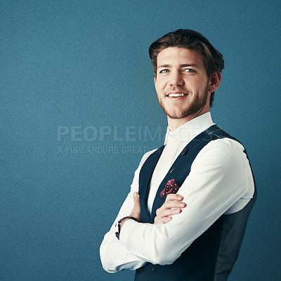 Buy stock photo Studio shot of a handsome young businessman standing with his arms crossed against a coloured background