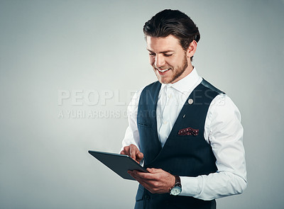 Buy stock photo Studio shot of a handsome young businessman using a tablet against a grey background