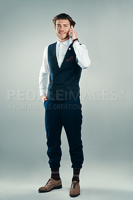Buy stock photo Studio shot of a handsome young businessman making a phonecall against a grey background