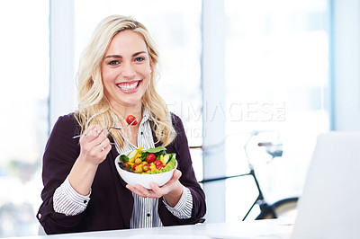 Buy stock photo Cropped portrait of an attractive young businesswoman eating a salad while working in her office