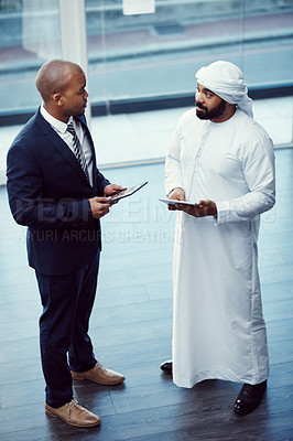 Buy stock photo Shot of two businessmen using digital tablets while having a discussion in a modern office
