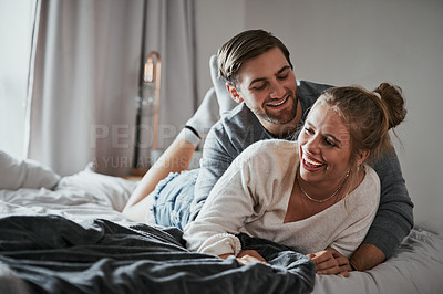 Buy stock photo Shot of a happy young couple spending quality time together in the bedroom at home