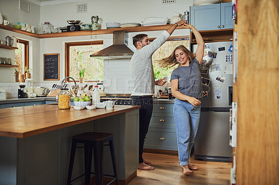 Buy stock photo Shot of a young couple dancing in their kitchen