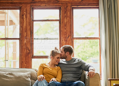 Buy stock photo Cropped shot of a young couple being affectionate on the sofa in the living room at home