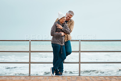 Buy stock photo Full length shot of an affectionate senior couple standing on the promenade at the beach