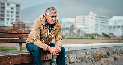Buy stock photo Cropped shot of a senior man looking depressed while sitting on a bench near the beach