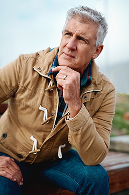 Buy stock photo Cropped shot of a handsome senior man looking thoughtful while sitting on a bench near the beach