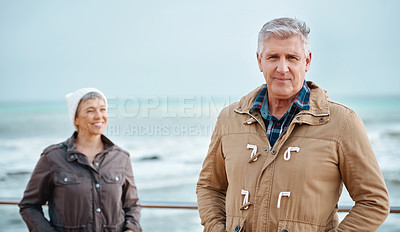 Buy stock photo Cropped portrait of a handsome senior man and his wife standing on the promenade at the beach