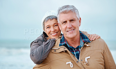 Buy stock photo Cropped portrait of an affectionate senior couple standing outside at the beach