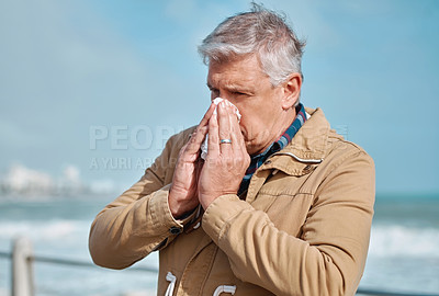 Buy stock photo Cropped shot of a senior man blowing his nose while standing on the promenade at the beach