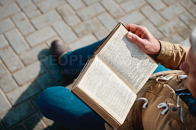 Buy stock photo High angle shot of an unrecognizable senior man reading his book while sitting on a bench on the promenade at the beach