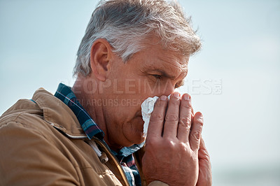 Buy stock photo Cropped shot of a senior man blowing his nose while standing outside at the beach