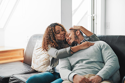 Buy stock photo Cropped shot of a young couple being affectionate on the couch in the living room at home