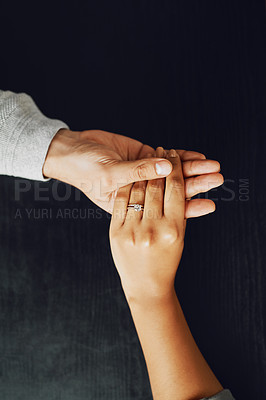 Buy stock photo High angle shot of an unrecognizable couple compassionately holding hands at a table