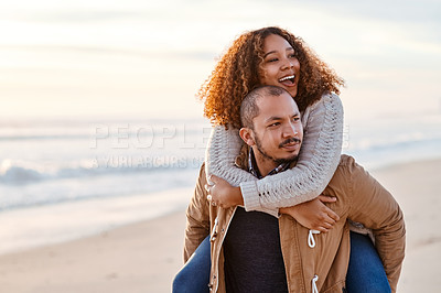 Buy stock photo Shot of a handsome young man piggybacking his girlfriend on the beach
