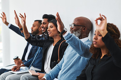 Buy stock photo Shot of a group of businesspeople sitting in line and raising their hands