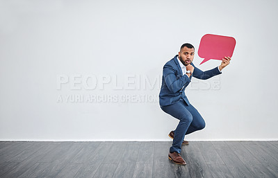 Buy stock photo Studio shot of a young businessman holding a speech bubble