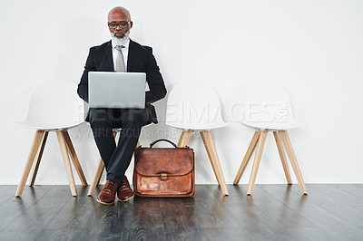 Buy stock photo Studio shot of a mature businessman using a laptop while waiting
