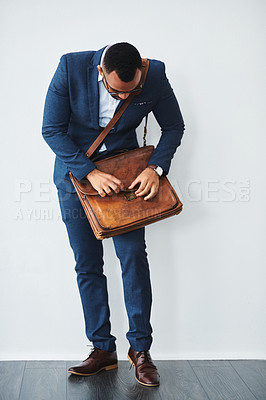 Buy stock photo Studio shot of a well dressed young businessman closing his bag