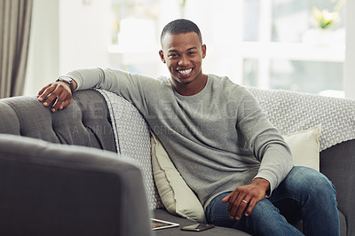 Buy stock photo Cropped shot of a handsome young man chilling on the sofa in the living room at home