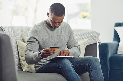 Buy stock photo Cropped shot of a handsome young man shopping online in the living room at home