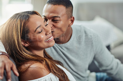 Buy stock photo Cropped shot of a young attractive couple being affectionate on the sofa at home