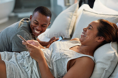 Buy stock photo Cropped shot of a young attractive couple using cellphones in bed at home