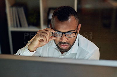 Buy stock photo Shot of a young businessman using a computer at his desk during a late night in a modern office