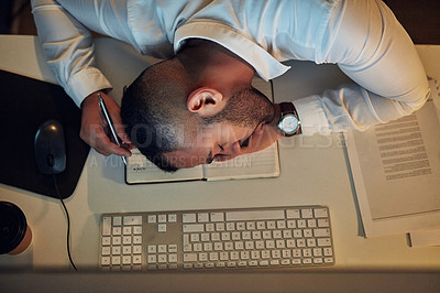 Buy stock photo High angle shot of an exhausted young businessman sleeping at his desk during a late night at work