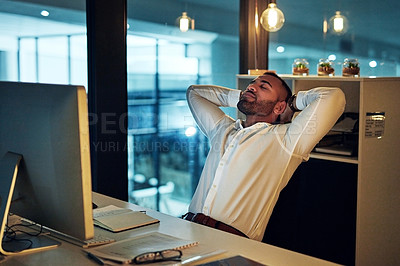 Buy stock photo Shot of a young businessman taking a break at his desk during a late night in a modern office